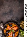 Small photo of Paella background, space for text. Paella in black pan with saffron rice, peas, shrimps, mussels, squid, meat. Seafood paella, traditional spanish dish. Paella on rustic black wooden table. Top view