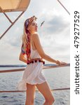 Small photo of Beautiful young girl with long blond hair dressed in nice white dress posing on the ship. She looks at the beautiful sea, clouds and mainland in the far distance. It is accompanied by a large seabird.