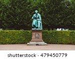 Small photo of Copenhagen, Denmark - September, 22th, 2015. Hans Christian Andersen statue in Rosenborg garden. Bronze sculpture of famous danish fairy tale writer amid green plants.