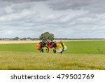 Small photo of Seville, Spain - May 7, 2016: Skydivers carries a parachute after landing at La Juliana Aerodrome. Skydive Spain is the skydiving center they fly up to 15,000ft, the highest altitude in Europe.