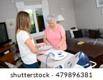 cheerful young girl ironing and ... | Shutterstock . vector #479896381