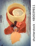 Small photo of Vintage photo, Cup of tea with lemon wrapped woolen scarf, warming beverage for flu and cold, decoration of autumnal leaf, rowan, acorn and alder cone