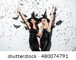 Small photo of Two happy young women in black witch halloween costumes on party over white background