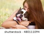Stock photo young dog owner girl plays with french bulldog puppy in park outdoor teen brunette female kissing 480111094