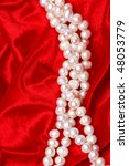 Small photo of Pearls necklace on DNA spial form on red velvet