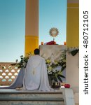 Small photo of Priest Kneel Down in front of an Altar with Golden Ostensory: Outdoor Church