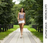 Portrait of young brunette woman in white short walking in summer park, outdoors