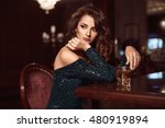 Stock photo beauty young brunette woman sitting at the bar with glass of whiskey in luxury interior 480919894