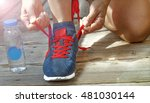 Small photo of Concept: healthy lifestyle, a record single-mindedness. Running shoes - closeup of woman tying shoe laces. Female sport fitness runner getting ready for jogging