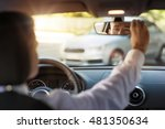 Man sitting in a car and adjusting rearview mirror, car interior - stock photo