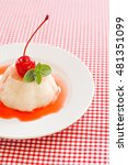 Small photo of White airy cream-mousse dessert with syrup, cherry, mint on a red background.