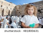 Small photo of The Jewish holiday of Sukkot. Cute little boy with long blond curls and blue eyes in blue skullcap. He stands at Western Wall of Temple