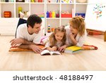 Happy family laying on the floor reading in the kids room - stock photo