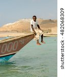 Small photo of SOCOTRA, YEMEN - JAN 12, 2014: Unidentified Yemeni man sits ion a boat on the beach of the Island of Socotra. Socotra Island is a UNESCO World Heritage Site