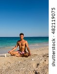 Small photo of Adult male meditation practicing in the morning on the beach, Lefkada island, Greece