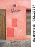 Small photo of PALMA, MALLORCA, SPAIN - AUGUST 29, 2016: Idem sign on red roughcast wall in Santa Catalina on a summer day on August 29, 2016 in Palma, Mallorca, Spain.