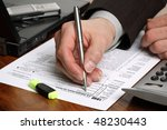 Filling in a 1040 individual tax form with calculator and laptop - stock photo