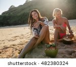 Two Young Women Sitting On The...