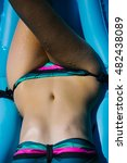 Small photo of Beautiful female body of young woman with perfect tanned abdomen and leg in colorful bikini laying on air bed in summer