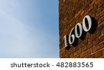 Small photo of Building with address sign saying 1600 against blue sky on a sunny day