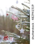 Small photo of Nice Christmas decorations on a tree outdoors. Snow and Christmas tree. Celebrating, winter and x-mas concept