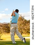 Full body young man outdoors playing golf hitting the bal - stock photo