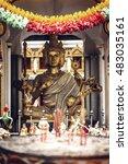 Small photo of Phra Phrom statue in Bangkok a street. Phra Phrom is the Thai representation of the Hindu god Brahma