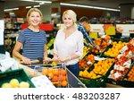 two positive woman choosing... | Shutterstock . vector #483203287