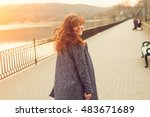 Small photo of Happy overweight woman walking the city street by the lake. Dynamic portrait of girl with wind on hair at sunset with sun flare effect