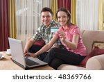Happy couple using credit card shopping online with laptop computer at home looking in camera - stock photo