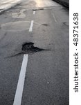 Potholes On A Road With White...