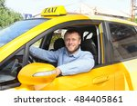 Small photo of Handsome taxi driver sitting in car