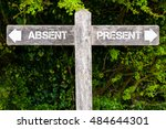 Small photo of Wooden signpost with two opposite arrows over green leaves background. ABSENT versus PRESENT directional signs, Choice concept image