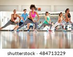 Small photo of Young black curly trainer with group training aerobic at gym