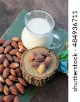 Small photo of Almond milk with almond on wood background