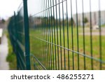 Small photo of green transparent metal fence with the prospect of leaving afar. inclosure background