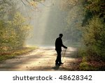 Older man through the country road in autumn forest in the light of the rising sun. - stock photo