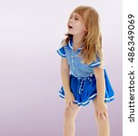 Small photo of On a purple background, smooth transition from dark to light. Cute little unkempt girl in a short blue dress. Girl looking to the side with his hands on his knees.