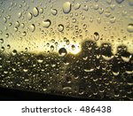 rain drops on the window, sunset in background, stormy clouds behind - stock photo