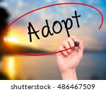 Small photo of Man Hand writing Adopt with black marker on visual screen. Isolated on nature. Business, technology, internet concept. Stock Photo