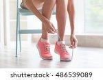 woman tying her pink sneakers | Shutterstock . vector #486539089