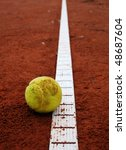 Yellow tennis ball on a red court - stock photo