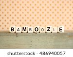 "Small photo of ""BAMBOOZLE"" printed on dice against rustic wood background and polka dots"