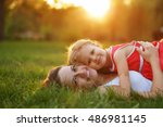 Small photo of Mother and daughter lying on the lawn. Family in the city park outdoors. Happiness of motherhood and childhood.