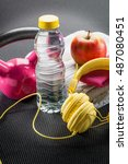 Small photo of aerobic exercise, sport lifestyle and workout concept - still-life of pink weight lifting, yellow earphones, towel and apple on grey gym mat, closeup