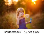 little girl blow bubbles at... | Shutterstock . vector #487255129