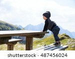 Cute baby child boy explore and looking at mountain view at the wood table. Picnic in the mountain. Family on a trekking day in the mountains. Mangart, Julian Alps, National Park in Slovenia, Europe. - stock photo