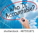 Small photo of Man Hand writing Who Is Accountable? with black marker on visual screen. Business, technology, internet concept. Modern business skyscrapers background. Stock Image