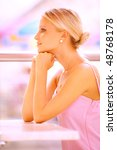 Small photo of Beautiful girl in pink dress sits at table, having leant chin against hands.
