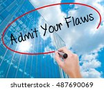 Small photo of Man Hand writing Admit Your Flaws with black marker on visual screen. Business, technology, internet concept. Modern business skyscrapers background. Stock Photo